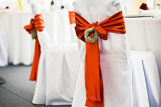 Красная свадьба. Красные банты на стульях.