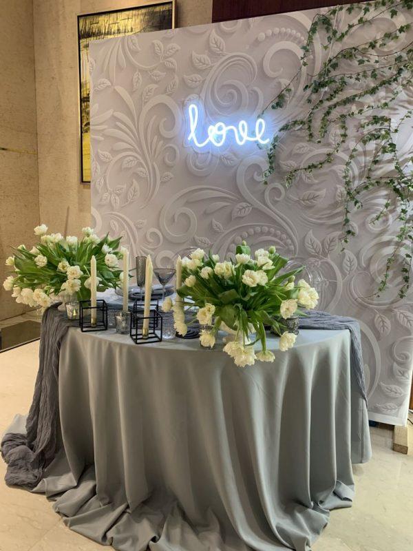 Оформление стола молодоженов для экспозиции на свадебной выставке. Неоновая вывеска, композиция из искусственных цветов. Фон за молодоженами